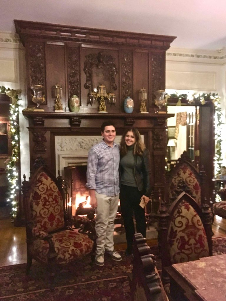 In from of the fire place in the gothic revival Buhl mansion, a scholarship recipient and her younger brother.